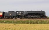 A steam train crossing the fens near Main Drove, Pymoor.. Britannia Locomotive