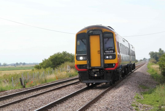 Diesel train approaching crossing X20 at Main Drove, Pymoor.
