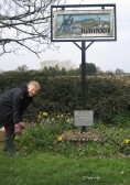 Tending the garden around the village sign at the crossroads in Pymoor.