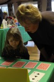 Pam Golding offers advice to her grandaughter Poppy as she plays a game at the Pymoor Cricket & Social Club Christmas Bazaar 2011.