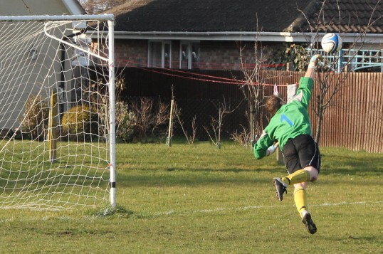 Little Downham FC goalkeeper, Paul Barrow, makes a save during a home fixture at the clubs ground in Pymoor, 2012.