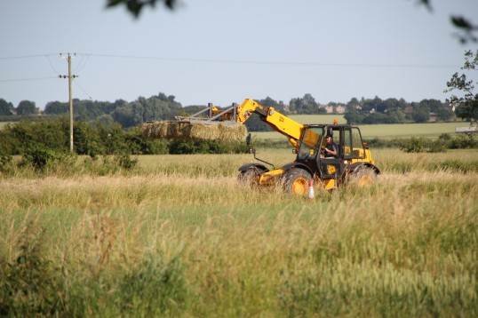 Norman Butcher driving a JCB with Hay Bales in a field off Pymoor Lane, Pymoor.