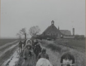 Schoolchildren make their way along a wet, muddy track across Pymoor Farm (circa 19750