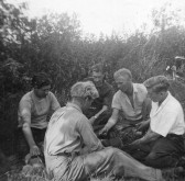 Bill McCauliff, Ivan Martin, Les Stevens, Hubert Stevens and Dennis Hall playing cards in a field off Pymoor Lane, circa 1950