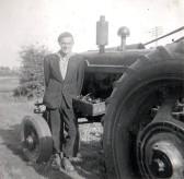 Derrick Godbold standing next to a Farmall H Model Tractor, circa 1950
