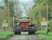 A large tractor makes its' way along Pymoor Lane, Pymoor, with a corn drill on the back, 2014