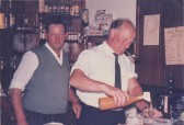 Ben Easy and Les Barker serving drinks behind the Pymoor Cricket Club bar, circa 1969