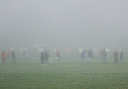 Ely Crusasers playing football in the fog at the Pymoor Cricket Club Ground, 2015