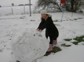 Bethaney Butcher rolling a large snowball in Pymoor, 2009