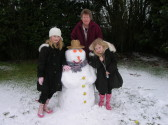 Laura, Joan and Bethaney Butcher with a Snowman in Pymoor, 2009