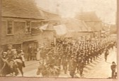 Army parade passing Rose & Crown public house, High Street, Ramsey