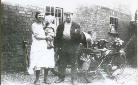 Ellen and Edward Stacey with one their children- Norah, Doris, John or Joan. Taken at Benwick Road, Ramsey Forty Foot.  Note the Motorcycle.