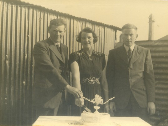 Leslie and Janet Edwards cutting the cake for their silver wedding anniversary. Clarence Edwards (son) is on the right. West Avenue, Ramsey