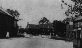 View of Bridge House, with Ivy Morriss in front of cottages and the George Public House on the right.