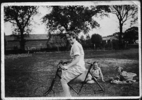 May Cole, Ted Howard and Joan Howard showing a home made four wheel bike at Ramsey Mereside Farm.