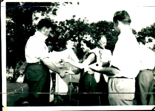 Ted Howard,receiving the winners cup for Tug-O-War,  as a member of the Mereside Fen Tigers, shaking hands with the Ramsey Beauty Queen.