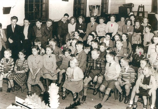 Children of Pondersbridge and Mereside being entertained in the village hall. Could be something to do with a royal event?,