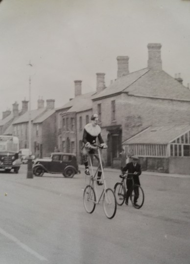 Man on tall bike part of Whitson Carnival 1951