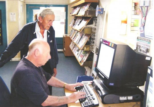 Sawtry Archive members working at the Library uploading material on the computer.