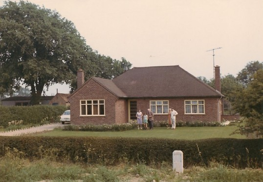 Mr. Mitchley and family outside their bungalow in Sawtry.