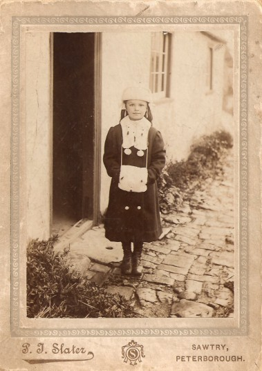 Ida Hughes of Sawtry, Photograph shows Ida outside a cottage in the Slype. Born 1906 died 1990. married Horace Sale in 1926.