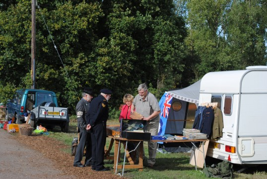 1940s Weekend in Holme Village. ARP Warden looking at the goods for sale.