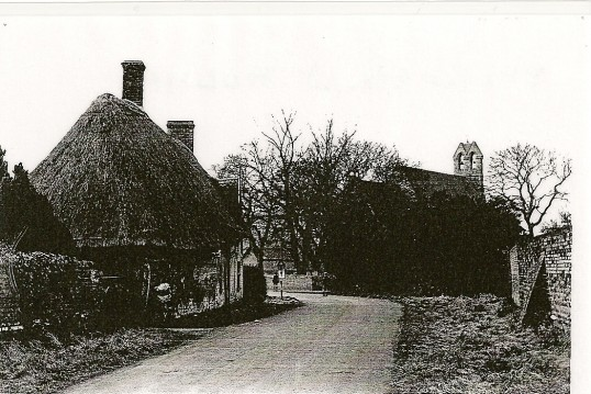Church Street Holme opposite Wells Way with view of the wall surrounding the kitchen garden of Holmewood Hall.