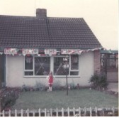 Hazel Ginn standing in front her bungalow, 7 Kings Parade Soham, that was decorated to celebrate the Silver Jubilee of Queen Elizabeth.