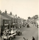 Part of the Carnival Parade passing along High Street, Soham. F.R Hutt's barber shop, is visible on the left.