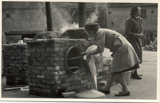 Mrs Manning cooking in an improvised oven during Civil Defence exercise Soham Exodus at Chippenham Park.