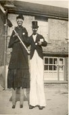 Reg and Frank Newman of Soham on stilts and dressed up for a local parade or event, possibly outside Bailey's (now Lea's Stores).