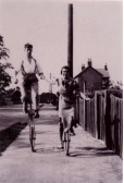 Reg Newman on his unicyle with May Boyden alongside, cycling along Fordham Rd, Soham.