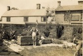 Original wall of The Place, Soham with (from l)  Angel pub opposite, Long's butcher's and home of Mr/Mrs Nicholls.The child is Dorothy Long (O'Dell).
