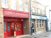 Carey's Amusements (once the Trustee Savings Bank) and Allders Opticians in November 2008 in South Street, St Neots