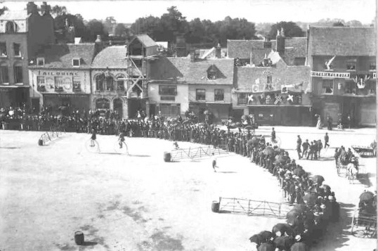 Victoria's Golden Jubilee in June 1887, in St Neots Market Square from the south.  2 men are on penny farthing cycles.