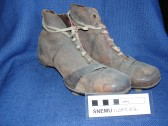 A pair of non waterproof leather football boots in St Neots Museum, from about 1960