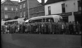 An outing by coach - people gathered outside C.G. Tebbutts in St Neots High Street in the late 1950s