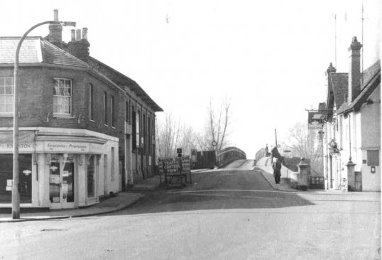 A view of St Neots Town Bridge from the Market Square with Dudeney & Johnstons Grocers (left), the Public Rooms (beyond the grocers) and the Bridge Hotel (right), in 1962/1963