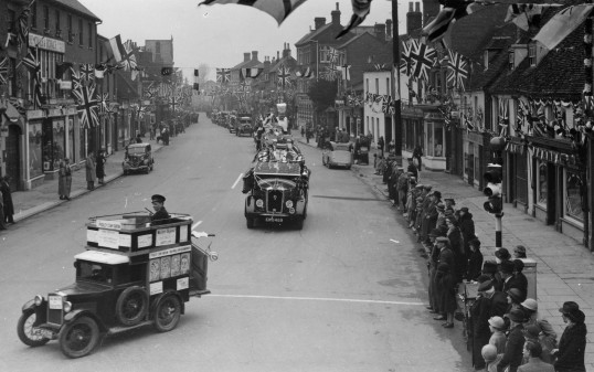 Procession of cars in St Neots High Street lined by spectators and Union flags in the 1930s