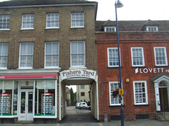 Fishers Yard entrance on the south side of St Neots Market Square in July 2010, with Connells and Lovetts Estate Agents on either side