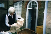 Museum volunteer checking clothing item in the Yard at St Neots Museum in New Street in September 2010