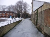 Henbrook stream frozen with Navigation Wharf, in Eynesbury, on the left  and disused ATS buildings on the right in December 2010 (P.Ibbett)