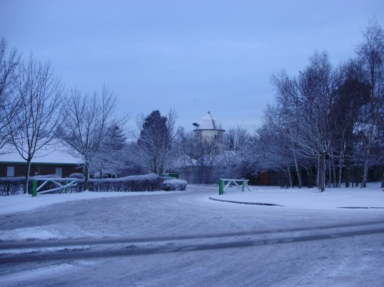 A snowy entrance to the Co-op Stores on the Great North Rd in Eaton Ford, with Duloe Windmill behind, in December 2010 (P.Ibbett)