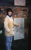 Bridget Ostler standing next to the flood level marker in South Street, St Neots, showing the height of the flood water in 1947.