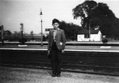 A young boy standing at St Neots Railway Station in the early 1950s, with the plate layers hut behind him