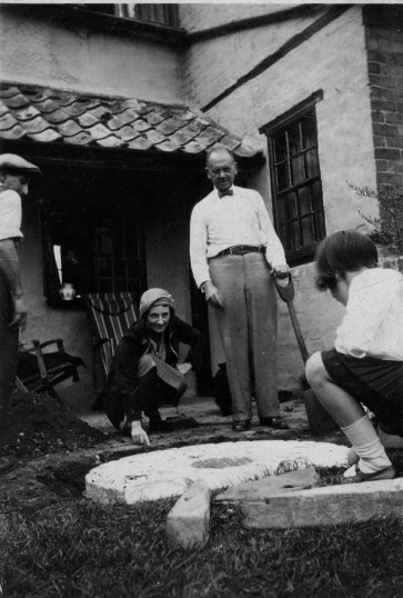 Austin James Barringer with Mrs Fedden and her daughter at Falcon Cottage, 164 Great North Rd, Eaton Socon with a mill stone from Sharmans mill, about 1948