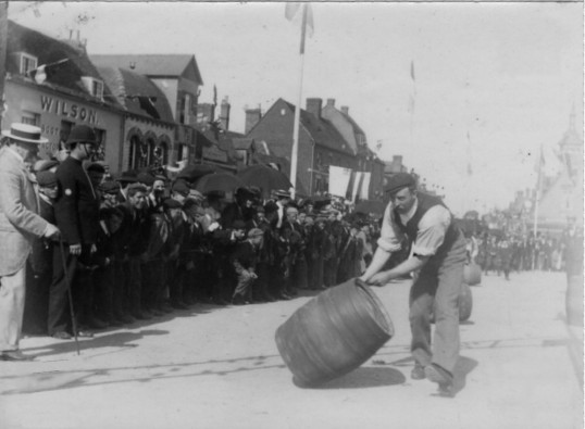 Rolling beer barrels in St Neots Market Square as part of the Queen Victoria's Diamond Jubilee Celebrations in 1897