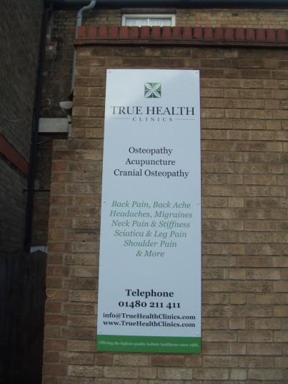 'True Health Clinic' board in Tebbutts Yard, St Neots