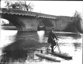 Mr Rowell (clothier, High Street, St Neots) with his homemade water bicycle by the town bridge.