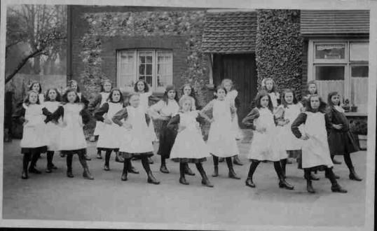 Postcard of girls in white school smocks dancing outside Eynesbury School, about 1905